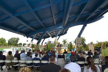People sitting under shade structure, listening to speaker at Anaheim Energy Shield