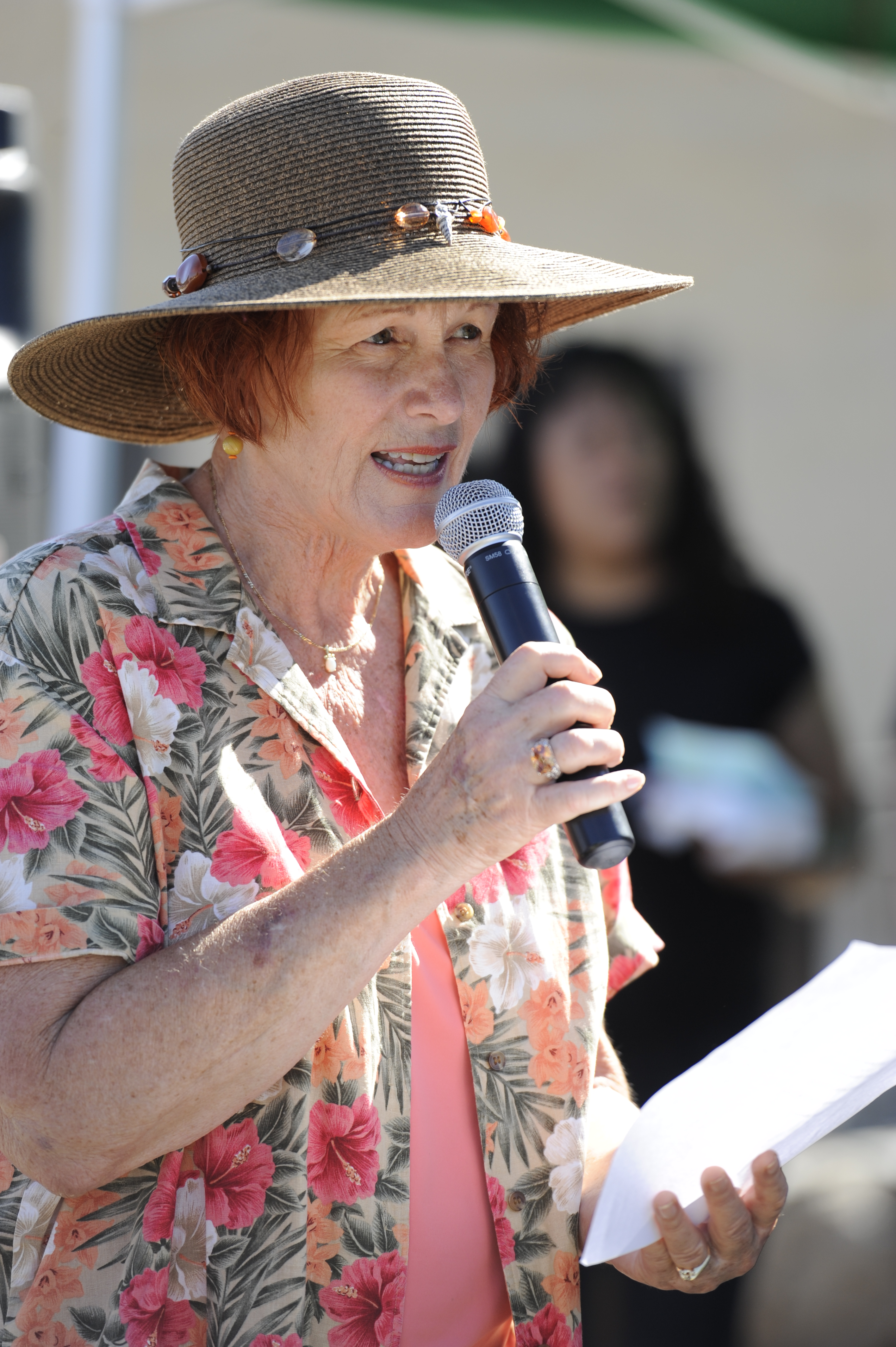 Woman holding a piece of paper and speaking into an microphone