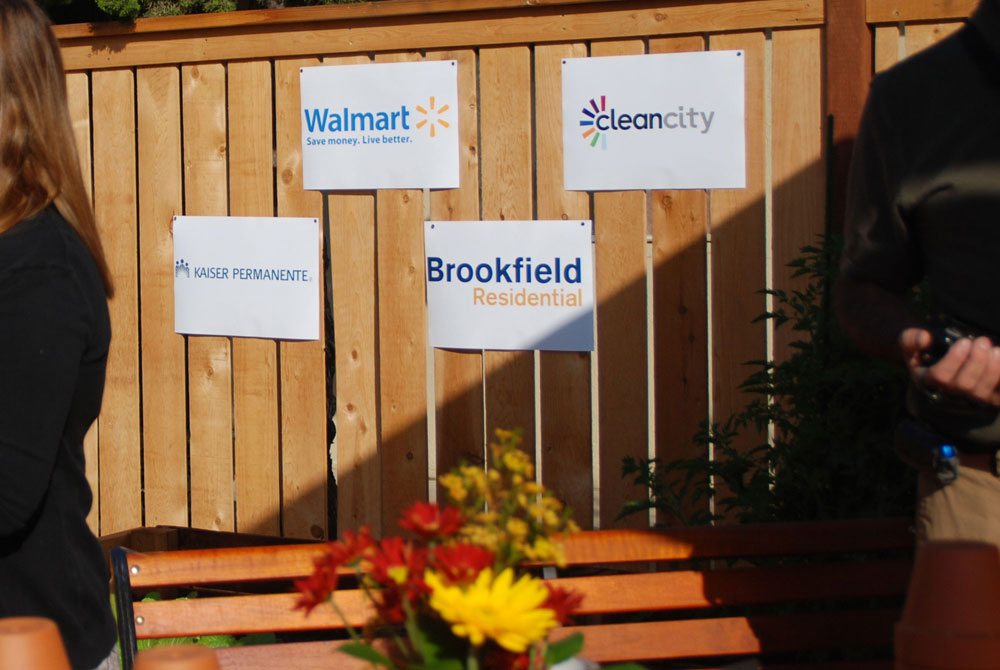 Four garden sponsor signs on the wall of the garden