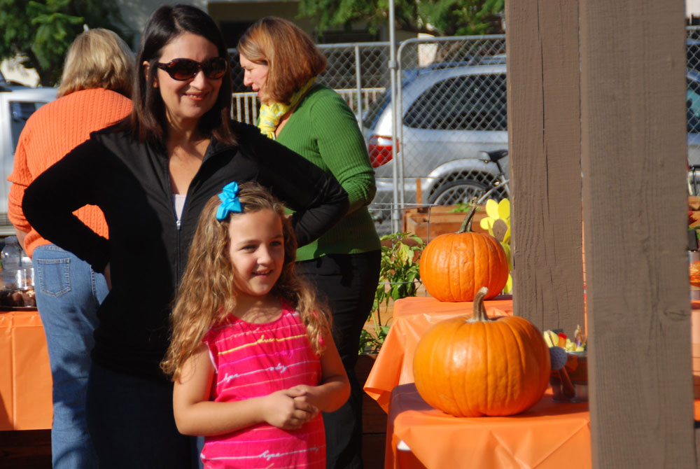 Mother and child standing next to the pumpkin table