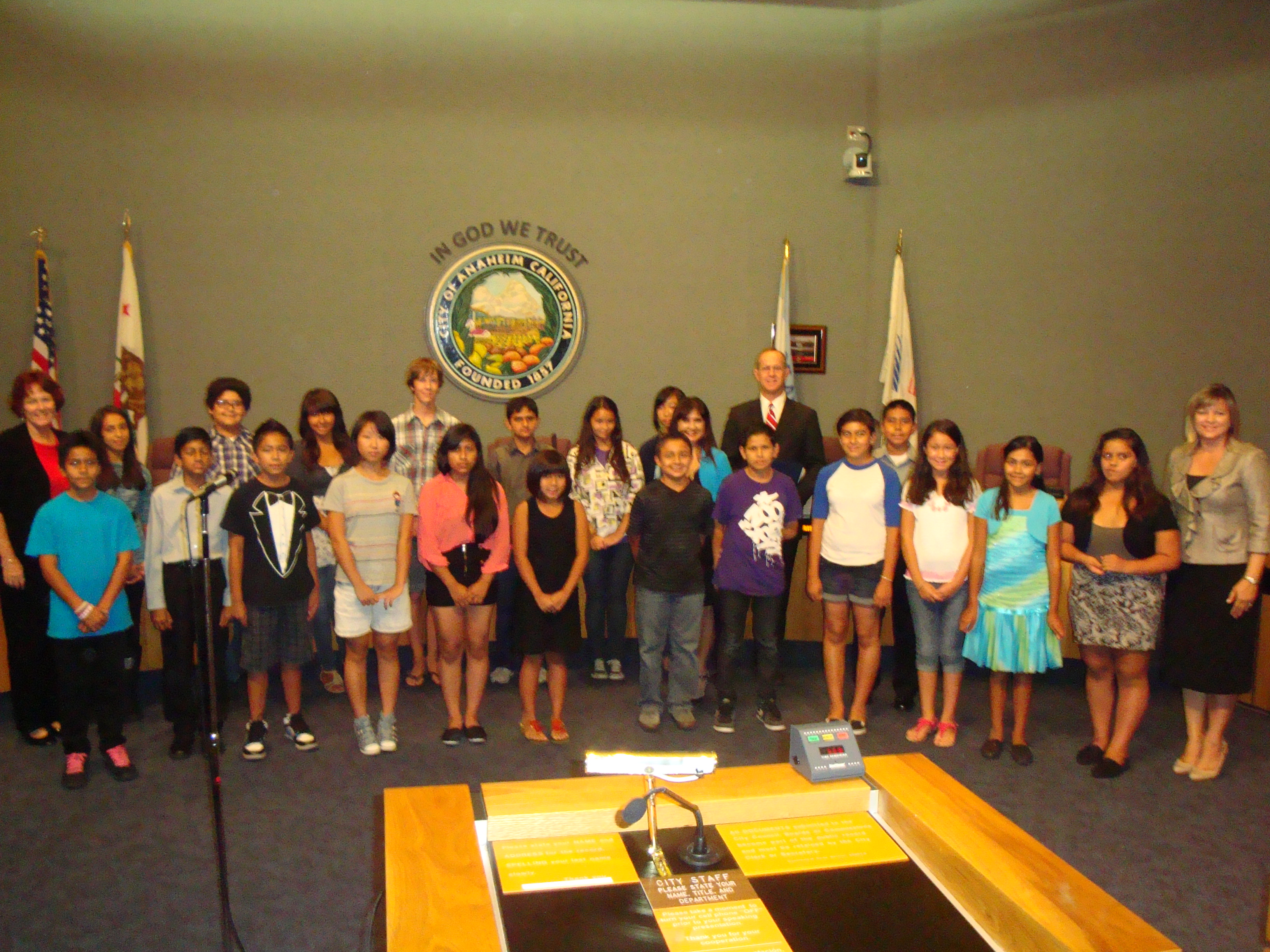 Large group photo with children at a city council meeting