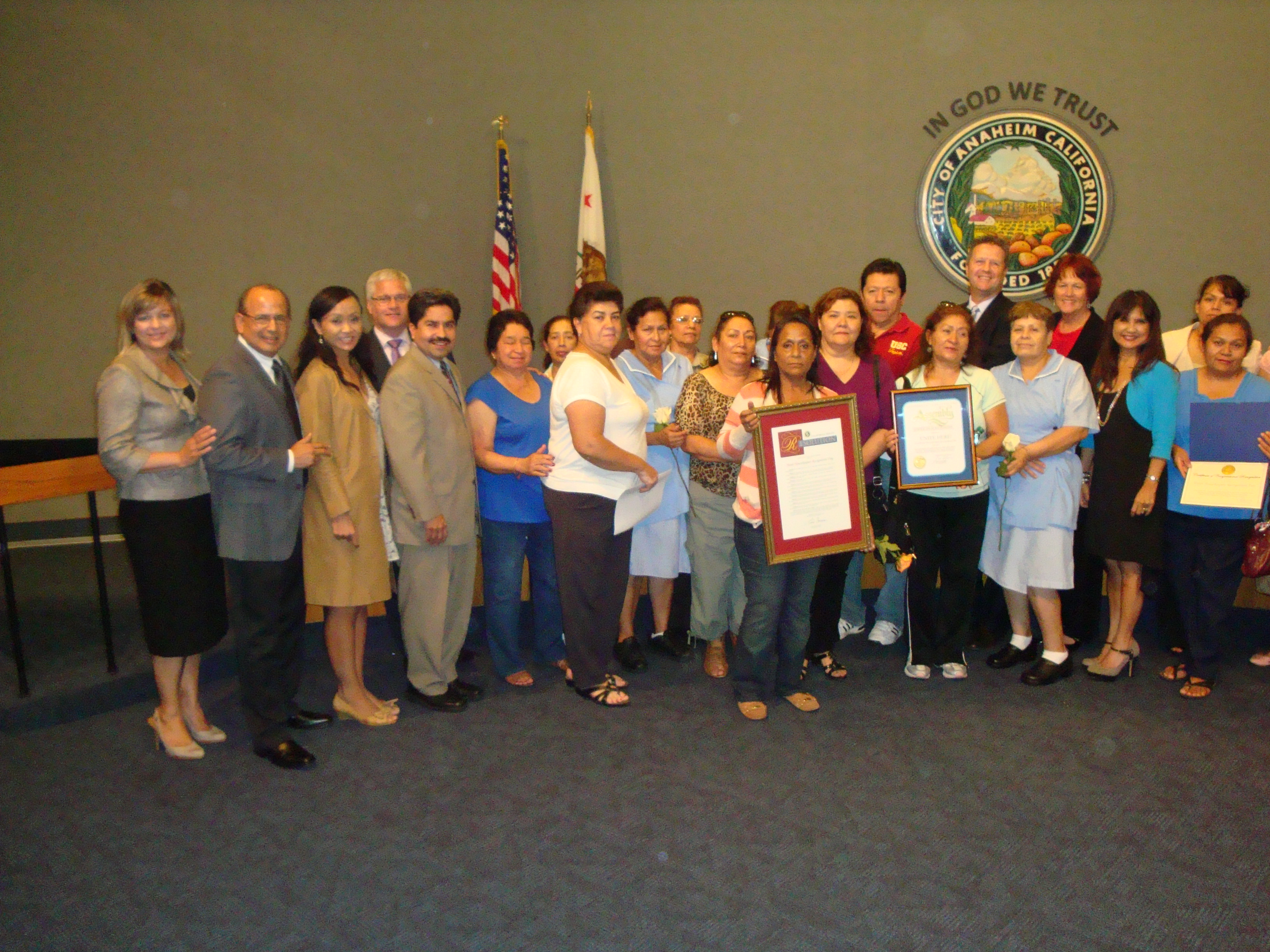Large group photo with people holding awards at a city council meeting