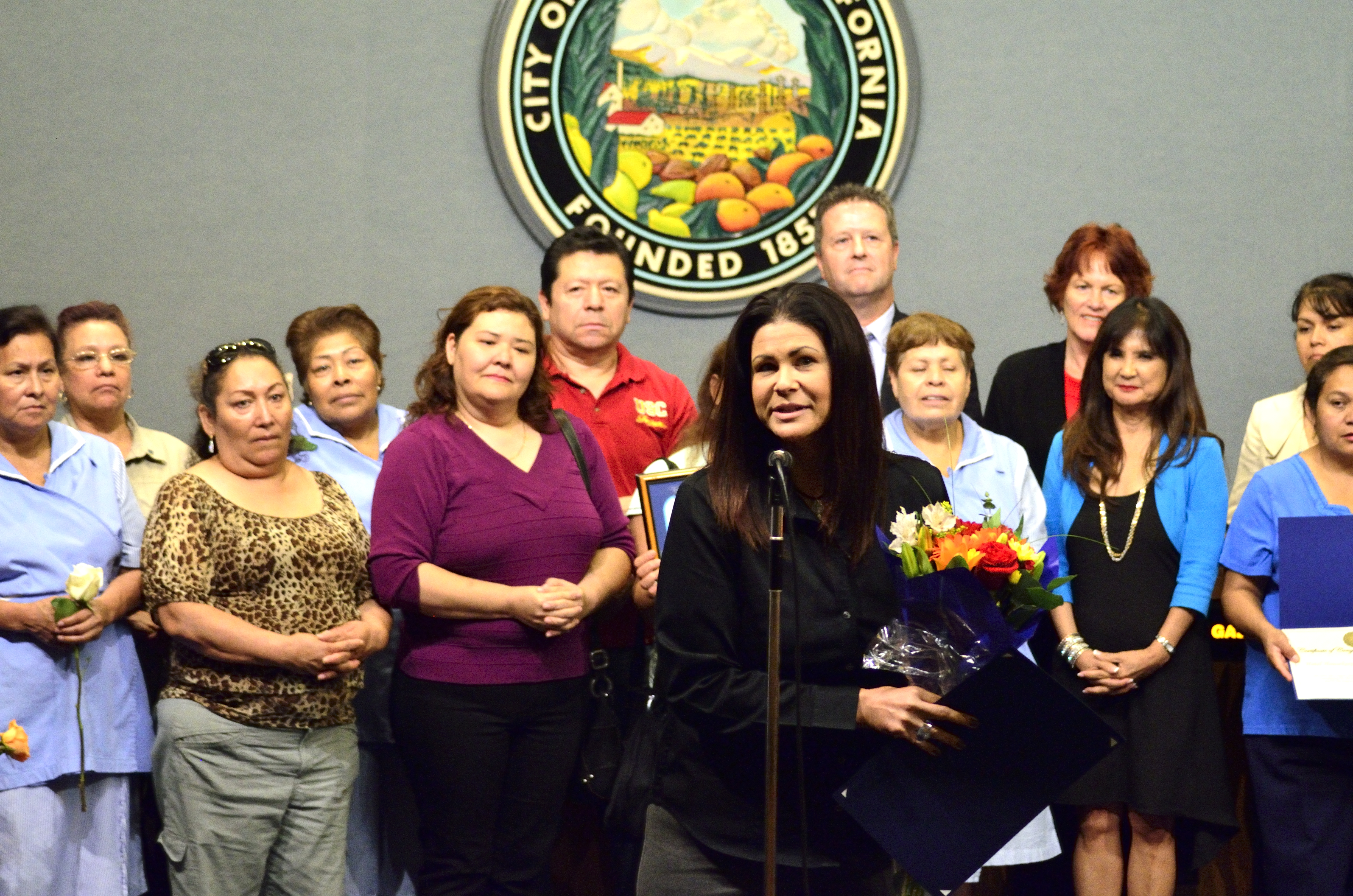 Woman speaking at City Council meeting while holding flowers