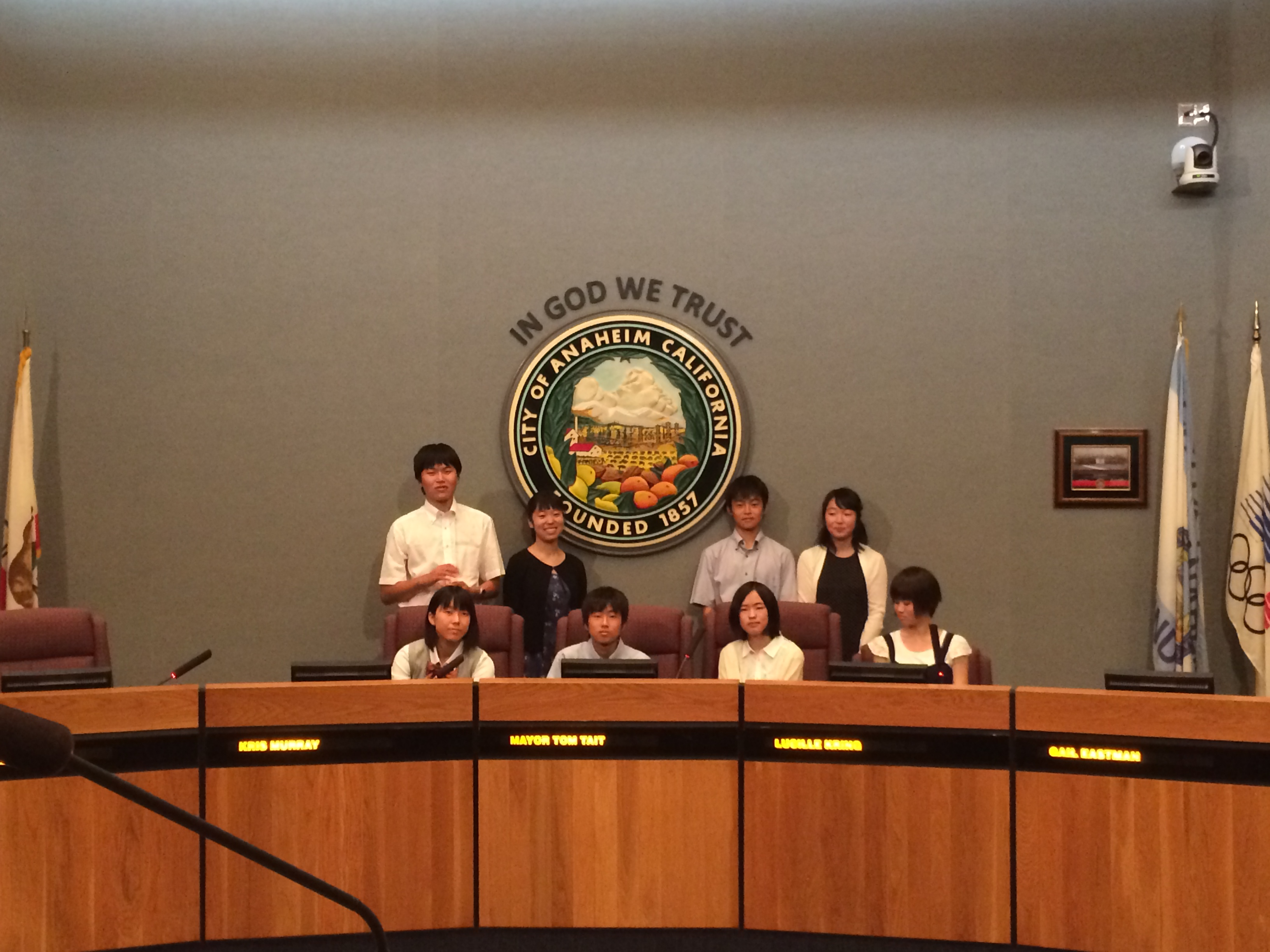 Students standing in front of the Anahiem City seal behind the curved table.