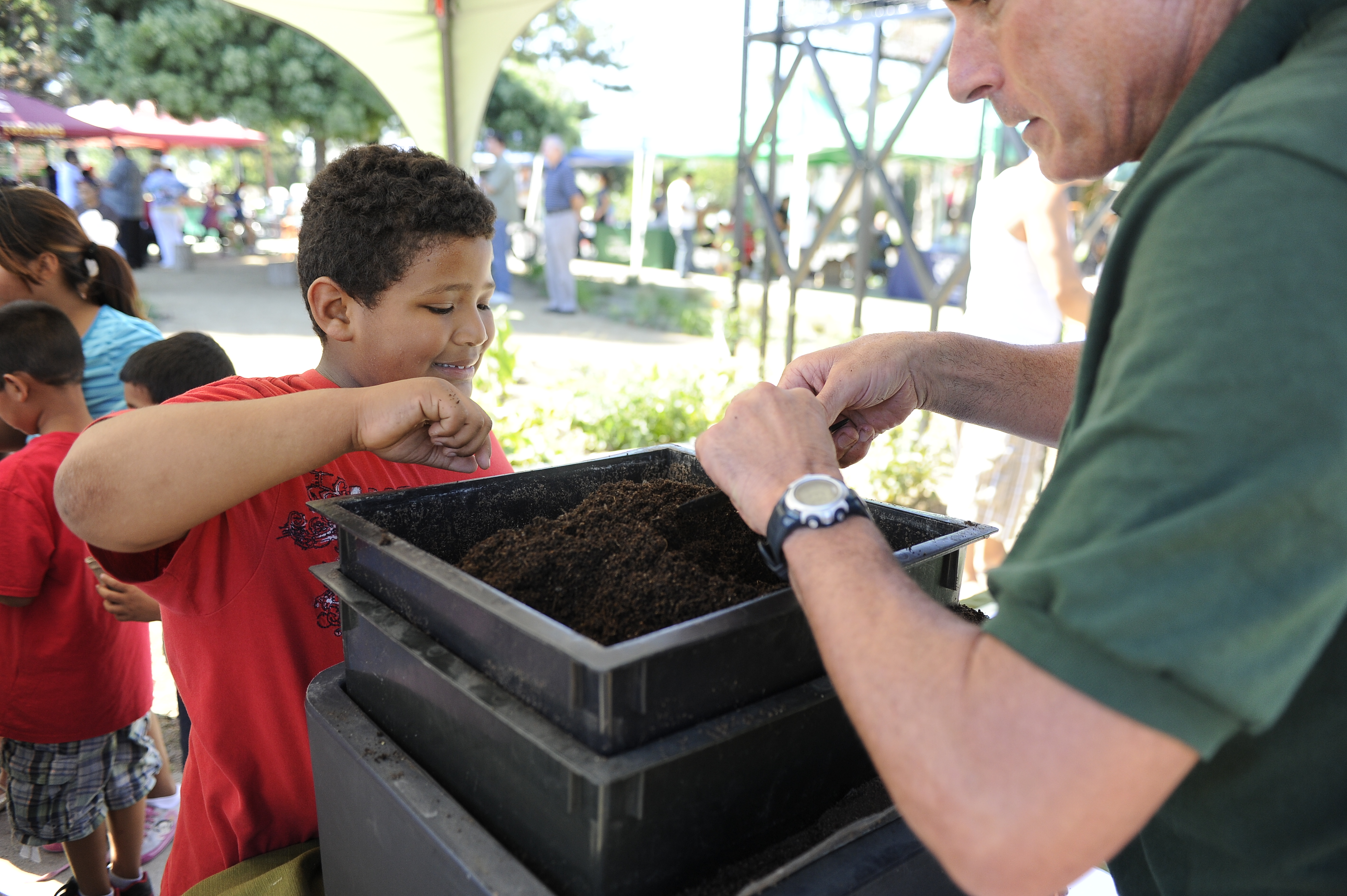 Young boy sticking his fingers in the dirt box while a man scoops dirt out